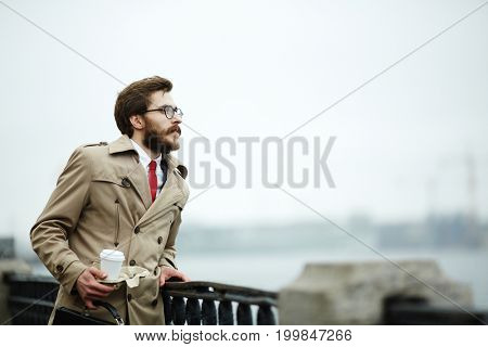 Pensive businessman with drink and briefcase leaning against fence by riverside on stormy day