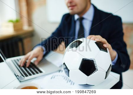 Soccer ball on workplace of businessman typing on laptop in office