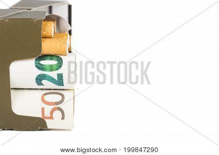 20 and 50 Euro banknotes bills cash with cigarettes. Box of cigarettes with bills in. Concept of cost of tabacco cigarettes. Front and top view close-up. On white backround