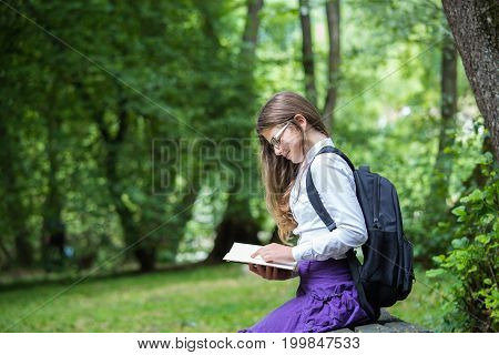Pretty Little Blonde Schoolgirl With Backpack And Long Hair Sitting On The Bench In The Nature Park