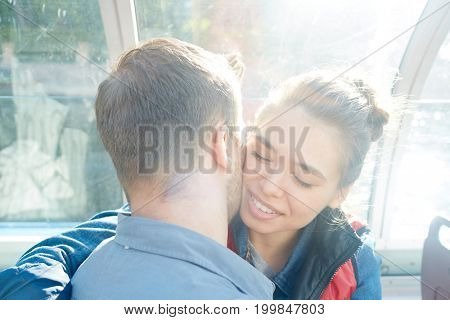 Young couple embracing and amorous man kissing his girlfriend on her cheek