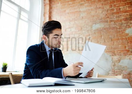 Young businessman reading financial document by workplace in office