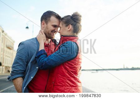 Amorous lovers embracing while standing face to face in urban environment