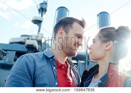 Young dates looking at one another on background of steamer