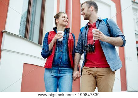 Affectionate sweethearts with drinks having walk along historical building in the city