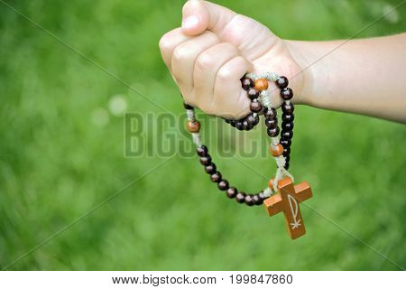 Rosary in child hands close up photo