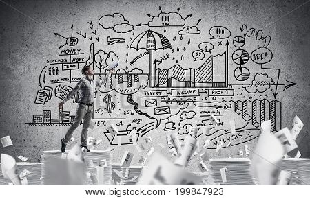 Man in casual wear keeping hand with book up while standing among flying papers with business-plan information on background. Mixed media.