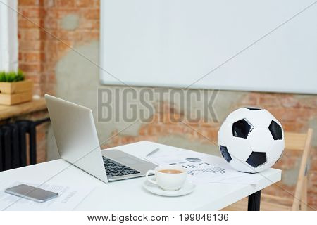 Workplace of businessperson, football fan, with modern gadgets, cup of coffee and soccer ball