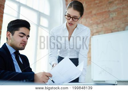Young co-workers consulting about signing contract with new partner in office after negotiation