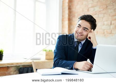 Happy young manager in suit sitting by workplaceand contemplating about something nice