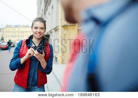 Young woman with photocamera going to shoot her boyfriend during journey