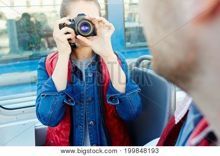 Young photographer shooting her boyfriend during cruise on steamer