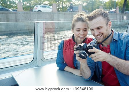 Amorous dates looking through shots in photocamera during their travel