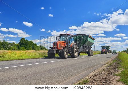 View on red tractor with trailer going to harvest wheat rye corn around gold wheat fields in summer. August wheat harvesting in Russia, Europe. Tractor on road