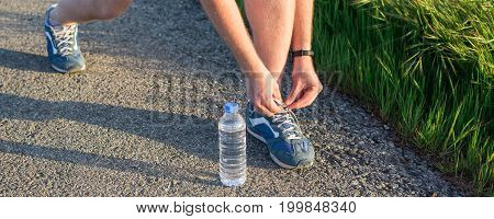 The athlete tying shoelaces. Sport and running idea concept. Young man runner tying shoelaces
