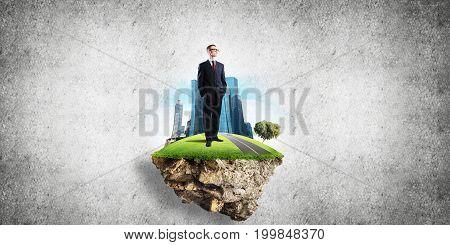 Elegant confident businessman standing on green floating island against concrete background