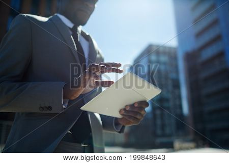 Modern trader with tablet working online in urban environment