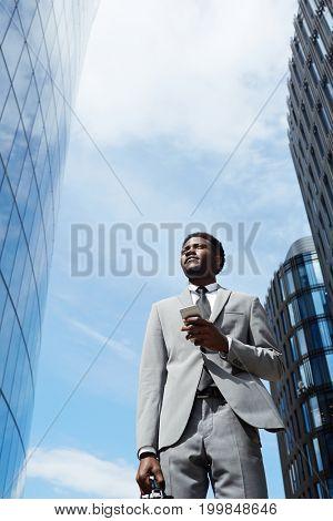 Elegant employer with smartphone between modern architecture