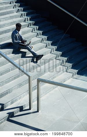 Mobile stock-broker sitting on stairs while looking through online financial data