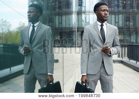 Elegant agent with smartphone and briefcase waiting for client outdoors