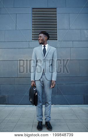 Happy African man in formalwear standing against wall of building