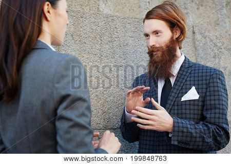 Young elegant managers having talk by wall of building
