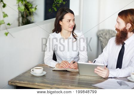Bearded economist making presentation of new ideas for business project to his colleague
