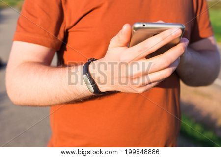 Sport, gadget, activity tracker and people concept - Male runner jogging outside looking at his wearable fitness bracelet
