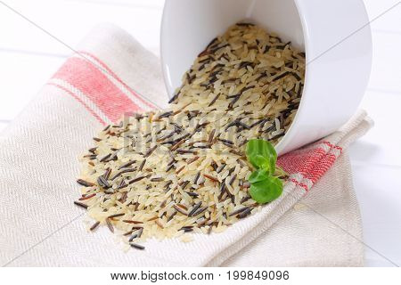 bowl of wild rice spilt out on place mat - close up