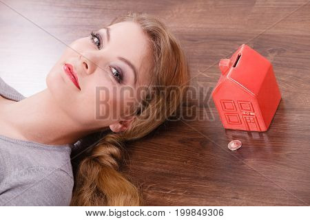 Home mortgage real estate property finances family concept. Woman lying with cash box. Young lady on floor next to piggy bank house.