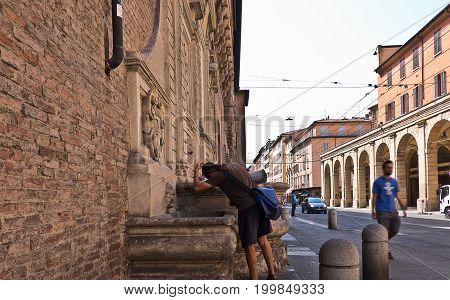 BOLOGNA, ITALY, 02 AUGUST 2017. A young man refreshes at a fountain in the historic center in bologna on a very hot day in summer, 02 august 2017