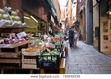 BOLOGNA, ITALY, 16 JUNE 2017 Seasonal fruit and vegetables on stalls at the open street market in the historic city of bologna with people on the background looking at the goods, 16 June 2017