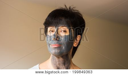 Beautiful adult woman with facial mask indoor