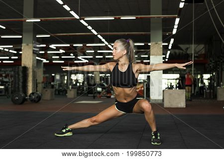 Beautiful young woman do sport exercises. Young woman stretching her legs and hands in gum. Blond sexy girl in gym.
