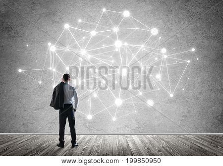 Back view of businessman looking at wall with drawn social connection concept