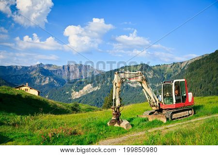 a small excavator is parked on a meadow in the austrian alps
