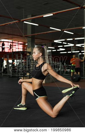 Attractive young woman in sexy sport clothing.Young blond slim fitness girl standing in moderm gym preparing for workout attractive professional trainer dressed in sports outfit making warming up exercises before starting pilates