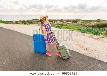 Happy cheerful traveler woman standing with suitcases on the road and smiling. Concept of travel, holidays, journey, trip.