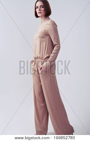 Vertical of good-looking supermodel posing in beige overalls in studio