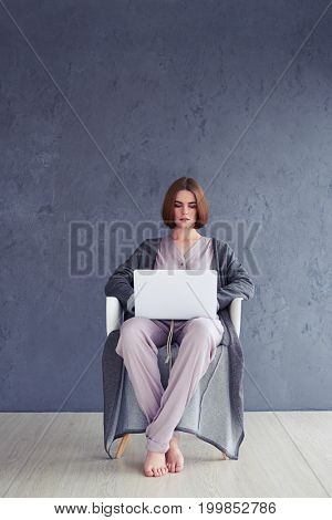 Wide shot of delightful girl sitting on armchair and surfing in laptop with copy space