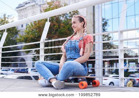 Wide shot of happy female having rest sitting on skateboard with copy space