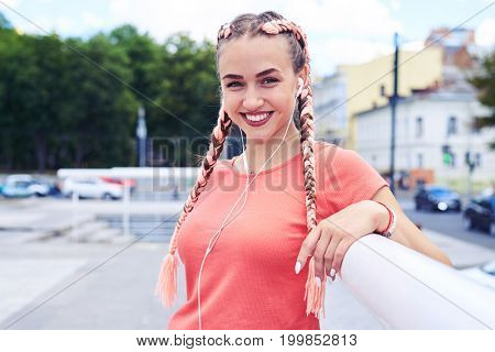 Mid shot of graceful woman leaning on handrail and listening to music with copy space