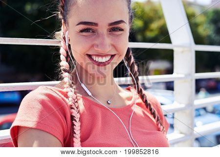 Close-up of amazing girl listening to music while sitting under handrail