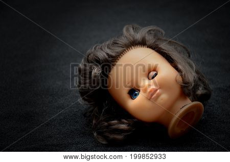 Doll head on black Sand dark background