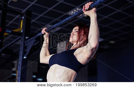 Close-up shot of fitness woman performing abdominal exercises on the horizontal bar