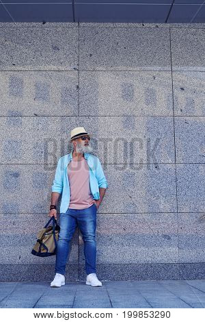 Elderly bearded man standing near wall of building in city, looking aside, having hand in pocket, another hand holding bag