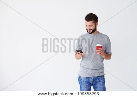 View of man holding cup of coffee, using Smartphone, smiling, having black beard, mid shot