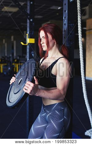 Side view of young fit girl raises weight plate, workout at gym exercise. Sport, fitness, lifestyle and people concept
