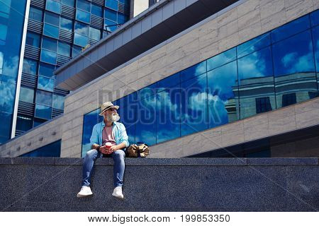 Wide shot of male in jeans and shirt enjoying city while drinking coffee and sitting under skyscraper with copy space