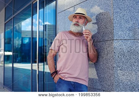 Mid shot of  bearded man with electro cigarette dressed in casual clothing, standing outdoors, narrowing eyes, holding hand in pocket